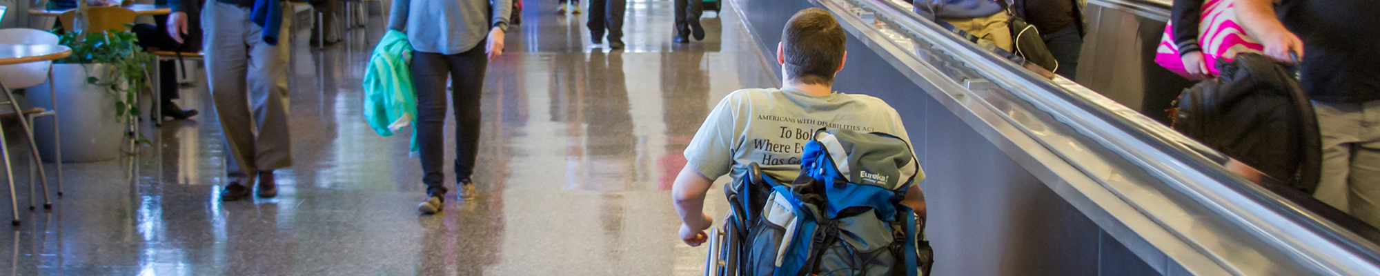 Image of a man in a wheelchair navigating through an airport terminal.