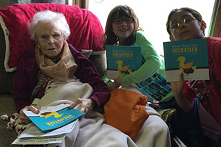 "Photo of Second graders refined their reading skills by preparing ""Show You Care – VOLUNTEER"" for readings with senior citizens, which included one-on-one conversations about lifetime volunteer opportunities."