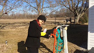 Photo of Linda Briles, Environmental Health Specialist with the Blackford County Health Department, collecting a well sample for BCCC's well testing project.