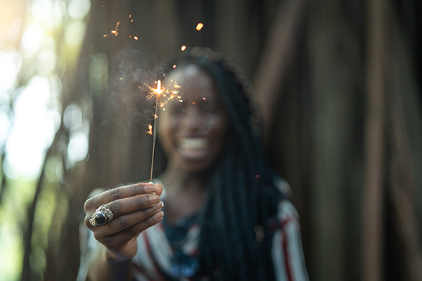 Photo of an African woman burning a sparkler firework.