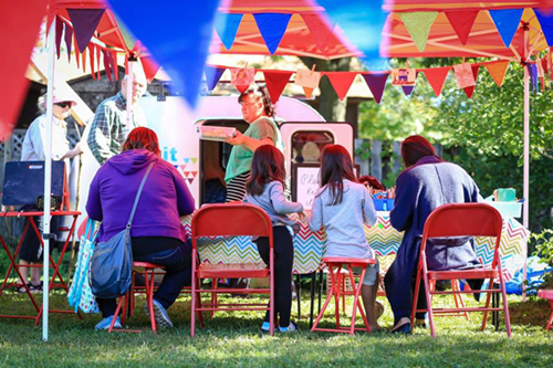 Photo of group eating under a colorful canopy in an outdoor park.