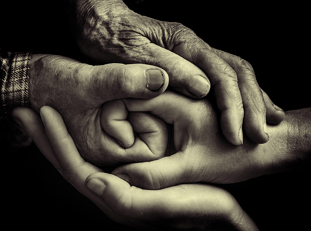 Image of a pair of older hands clasping a pair of younger hands.