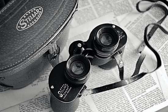 Black-and-white image of a pair of binoculars resting on a newspaper page.