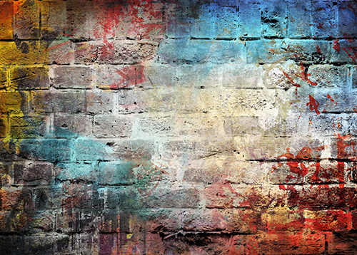 Photo of brick wall with multi-colored paint on it.