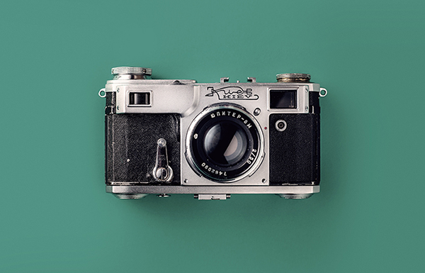 Image of a vintage still camera over a solid green background.