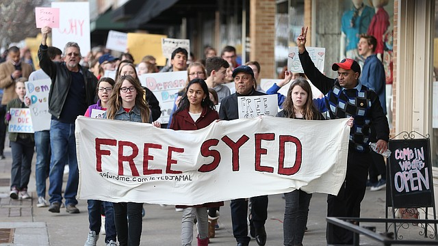 Photo of Naheen Jamal, 12-year-old daughter of Syed Jamal, center, flanked by her friends Elizabeth Anderson, left, and Anna Anderson as they lead a Free Syed Jamal march on Thursday, Feb. 8, 2018 at Lawrence Creates.