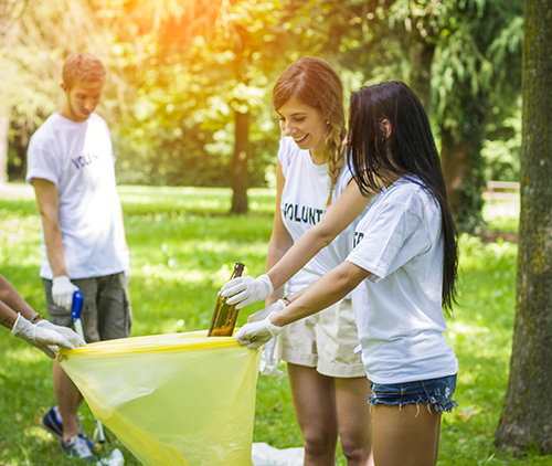 Image of young men and women cleaning up a park.