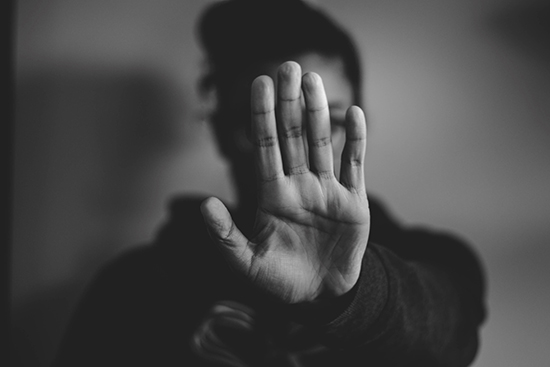"Black-and-white image of a person's hand out in front of their face as if to stay ""stop!"""