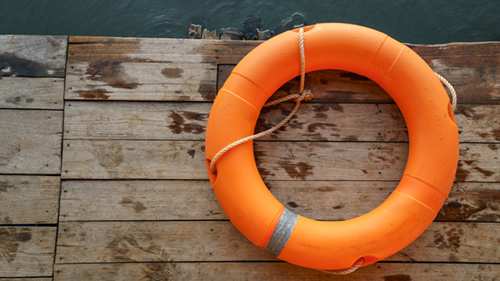 Image of an orange life preserver on a dock overlooking water.