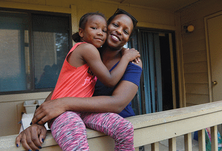 Photo of a mother and daughter hugging on a front porch.
