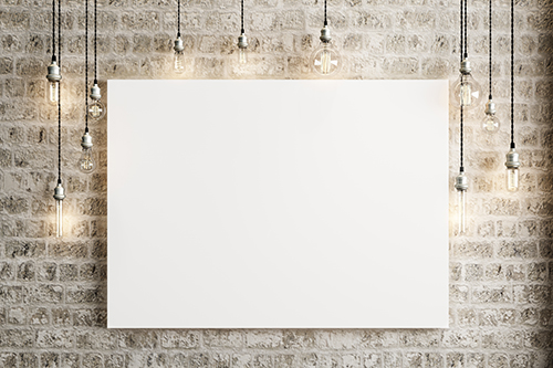 Photo of a blank canvas hanging on a brick wall with exposed lightbulbs around it, suspended from the ceiling.
