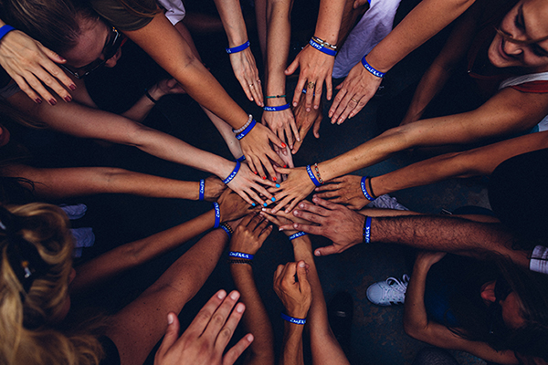 Image of a group of diverse people in a huddle, with their hands reaching together in the center of the group.