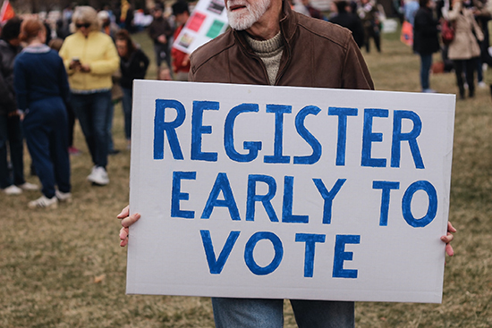 "Image of man holding a sign, saying ""Register to Vote."""