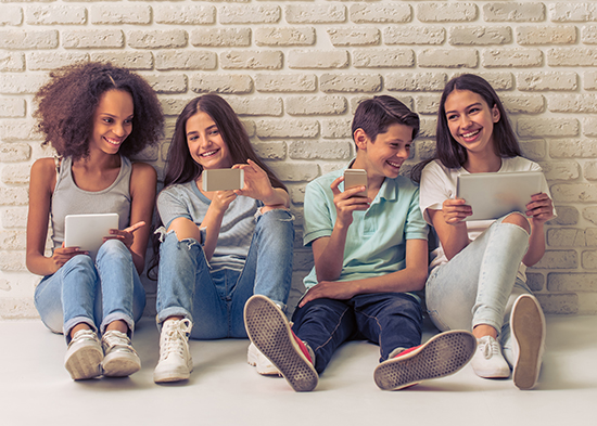 Photo of teenagers with gadgets sitting on the floor against a brick wall.