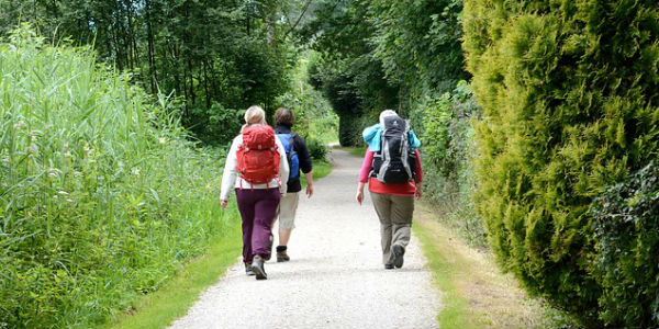 Image of ladies with hiking gear walking down a rural, woodsy lane.
