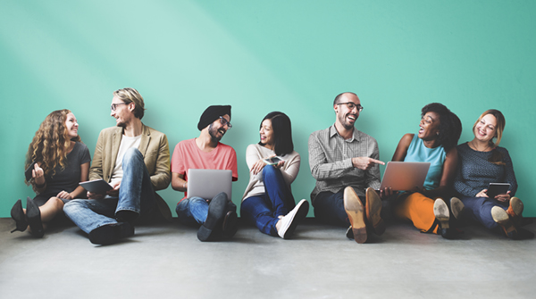 Image of diverse young adults socializing with laptops while leaning against a wall.