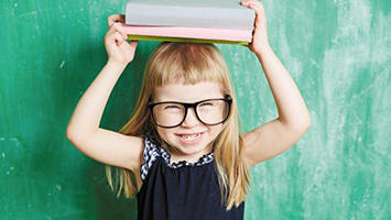 A little girl with glasses holding a stack of books on her head.