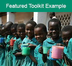 """Image of African children holding drinks with the text """"Featured Toolkit Example"""" above it."""