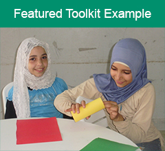 """Two Palestinian girls at a table with the text """"Featured Toolkit Example"""" above it."""