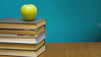 A stack of books with a green apple on top.