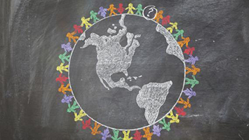 Chalk image of the world with colorful children cutouts circling it.