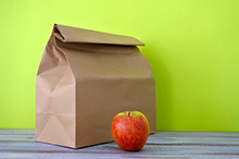 Photo of brown paper bag lunch with apple.