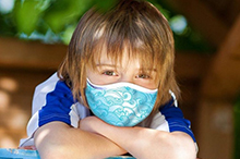 Photo of young boy wearing surgical mask with waves on it.