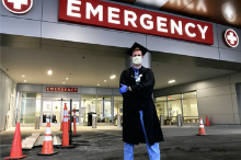 Thumbnail of a doctor wearing a graduation gown and cap over scrubs.