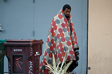 Image of African American homeless man walking on a sidewalk with a blanket wrapped around him.