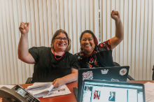Thumbnail of two smiling women each with one hand raised in a fist.