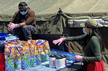 Photo of volunteers wearing masks, unloading supplies from a truck.