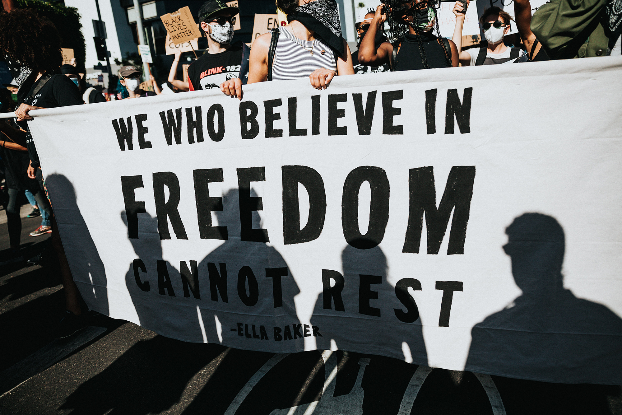 "Image of protestors marching, carrying a banner that says, ""We who believe in freedom cannot rest."""