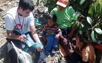 "Photo of Ricardo Lewis, Nutre Perú volunteer, reading the story of ""El Escuadron Clorito"" to a family during a home visit at the family's orchard."