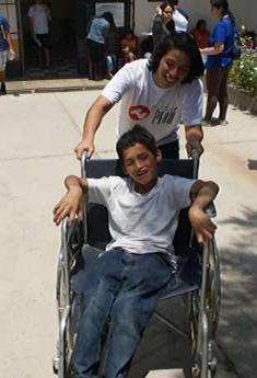 Photo of Gabriel Torres, Nutre Perú volunteer, having fun with Richard a child with cerebral palsy from Catahuasi.