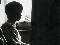 Photo of woman staring out of a window.