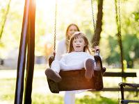 Photo of a disabled girl in a park on a swing.