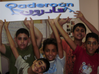Photo of boys holding a sign saying Qaderoon.