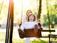 Disabled girl on a swing in a park.