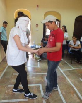 Photo of a blindfolded woman and a boy doing an exercise in front of others.