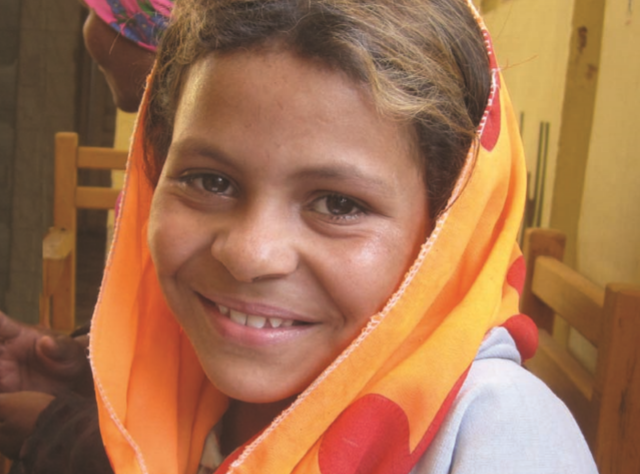 Image of smiling girl with colorful head scarf.