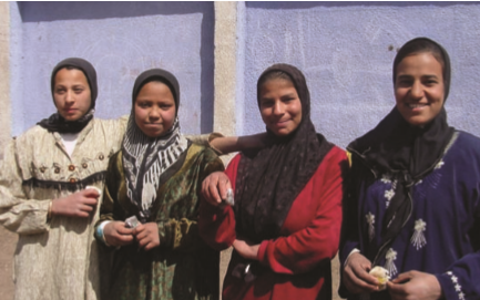 Image of a group of women smiling outside.