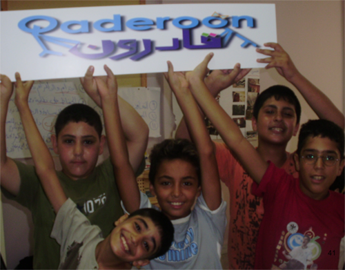 Image of young students holding Qaderoon sign.